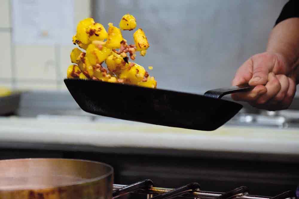 Geschwenkte Pfanne mit Bratkartoffeln
