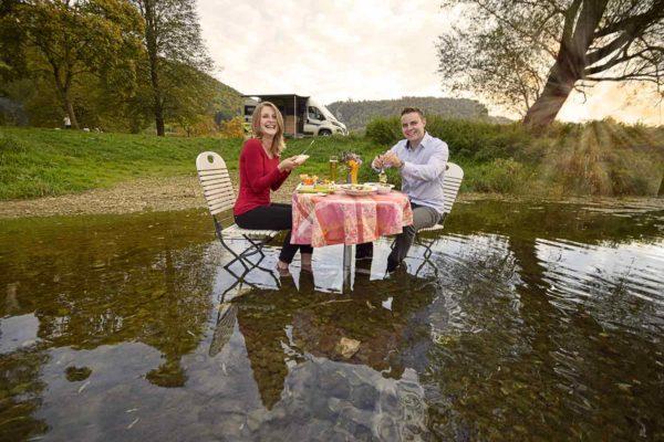 Paar isst in der Donau vor Wohnmobil